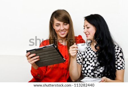 Two young woman using tablet pc