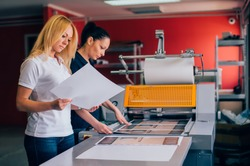 Two young woman working in printing factory. Printing Press