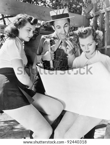 Two young women and a man looking at architectural plans