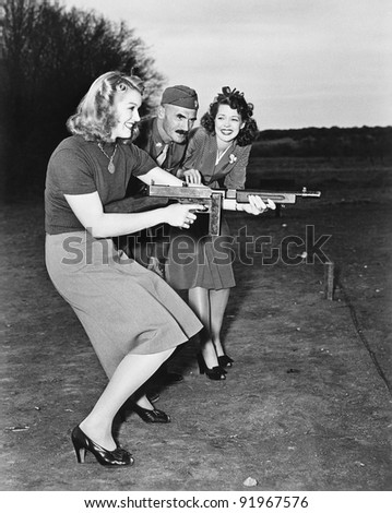 Two young women and a soldier trying out a machine gun