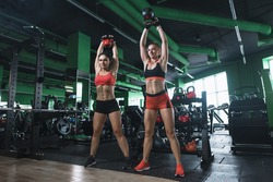 Two young women are doing shoulder presses with kettlebells