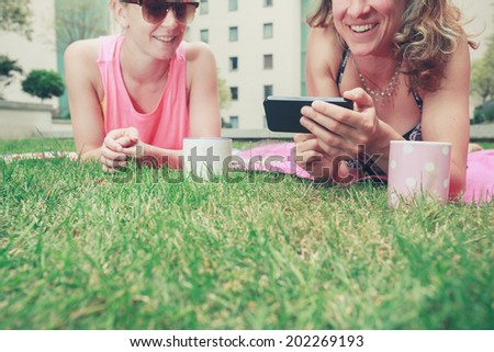 Two young women are laughing and smiling as they look at a phone outside