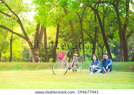 Two young women asians sitting on the grass and smiling in the park with Classic pink bike - Shutterstock ID 594677441