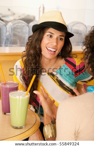 Two young women at a cafe drinking frozen beverages. Vertical shot.