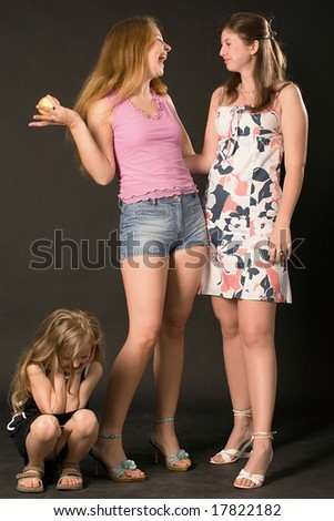 two young women chatting with smiles and sad little girl sitting near on black background