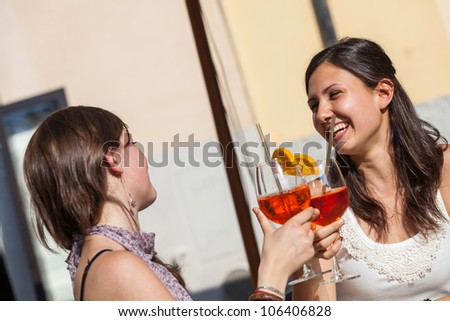 Two Young Women Cheering with Cold Drinks