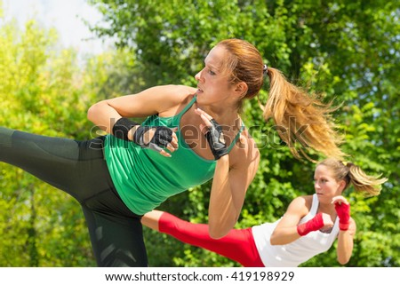 Two young women demonstrating side kicks in taebo training