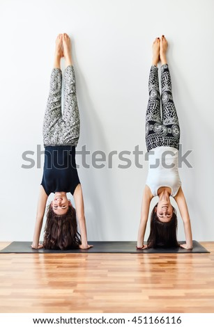 Two young women doing yoga handstand pose. Adho Mukha Vrksasana