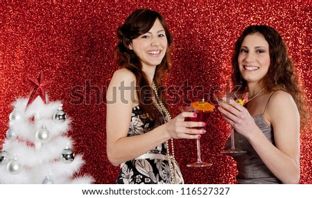 Two young women drinking cocktails and having fun with a christmas tree and a red glitter background.