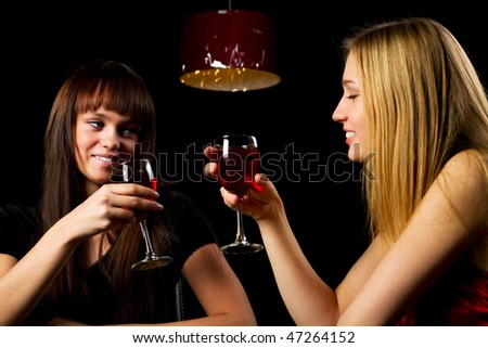 Two young women drinking red wine in a bar.
