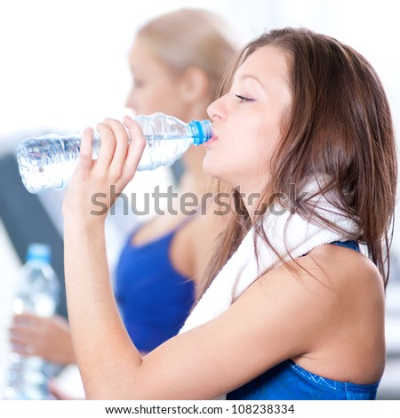 Two young women drinking water after sports. Fitness gym.