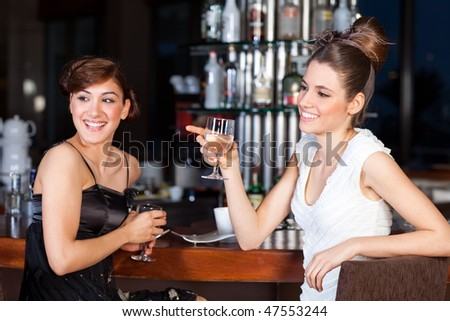 Two young women drinking water at bar