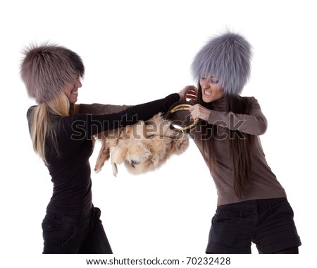 Two young women fighting for magnificent fur's bag on a white background. Sale.
