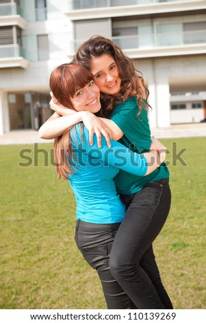 Two young women friends relaxing at the park
