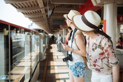 two young women friends travelers with backpack and camera missed subway and commuter waiting for next. girls tourist standing on outdoor platform in metro station looking for train arrived driving
