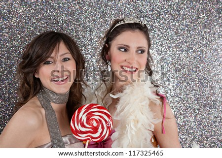 Two young women having a party and eating candy against a silver glitter background.