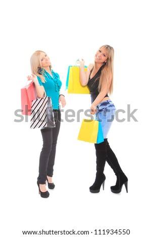 Two young women holding shopping bags isolated on white background