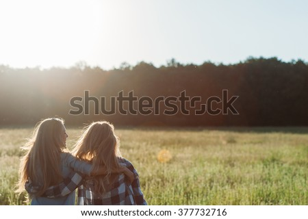 Two young women hugging at sunset.  Back view. Best friends