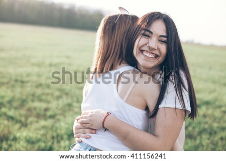 Two young women hugging outdoors. Asian girl looking at the camera and smiling. Best friends