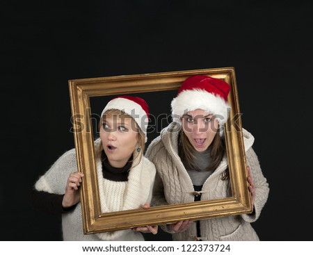 two young women in a frame, on black background