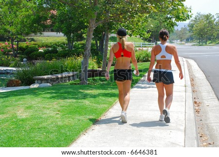 Two young women in exercise clothing on an walk down a pretty street.