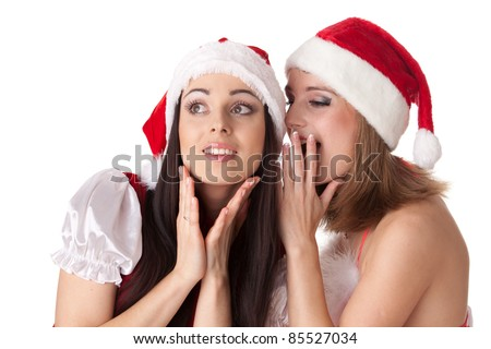 Two young women in Santa costume on a white background. Female secrets.