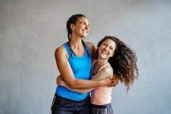 Two young women in sportswear laughing and standing arm in arm together in a gym