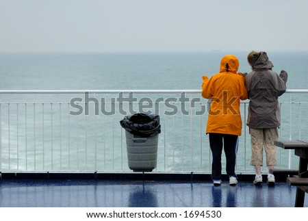 Two young women, in the rain, looking over the rail at a grey sea and waving. A container ship can just be seen on the horizon. Maybe they know someone on the ship.