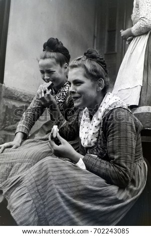 Two young women in traditional clothing eating bread and laughing