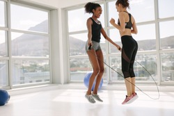 Two young women jumping together with skipping rope in fitness studio. Mixed race female friends workout together in gym with jumping rope.