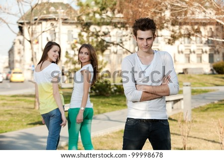 two young women looking at a young man, in the park