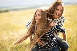 Two young women making fun outdoors