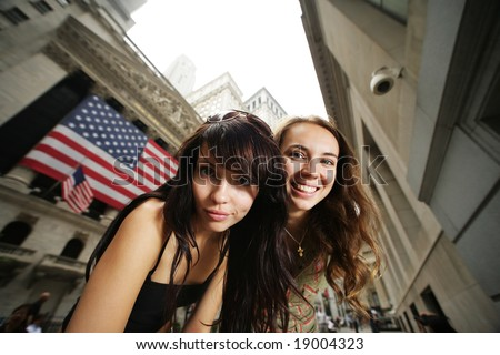 Two young women near New York Stock Exchange. Wide angle portrait.