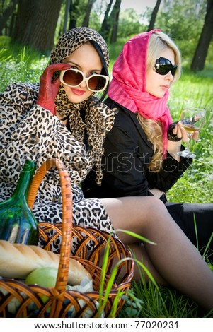 Two young women on a picnic in summer park vintage style series