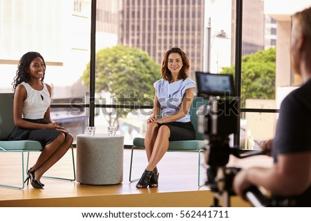 Two young women on set for the filming of a TV interview