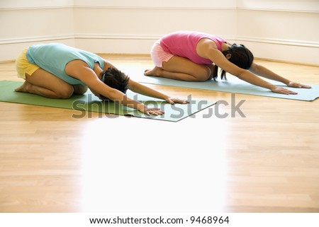 Two young women on yoga mats doing child's pose.