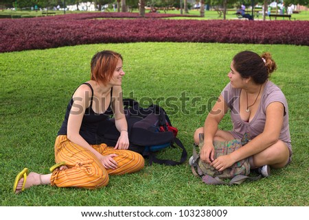Two young women (one Peruvian, the other European) talking in a park in Miraflores, Lima, Peru