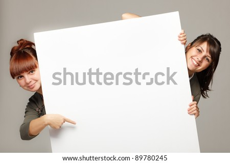 Two young women peeking over edge of blank empty paper billboard with copy space for text, over grey background