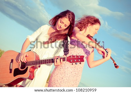 Two young women playing guitar and violin outdoors on the field in summer evening under the stormy sky. Split toning.