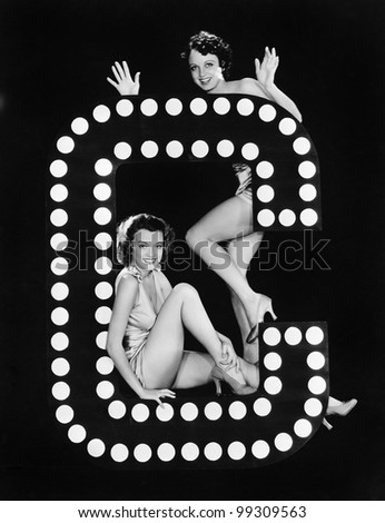 Two young women posing with the letter C - stock photo
