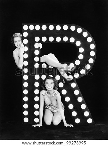 Two young women posing with the letter R