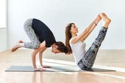 Two young women practicing yoga poses and asanas. Partner yoga