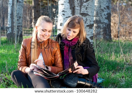 Two young women reading magazine in the park