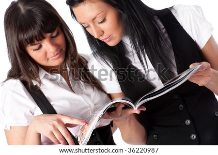 Two young women reading magazine. On white background.