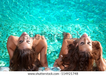 two young women relax and take sunbath in swimmingpool