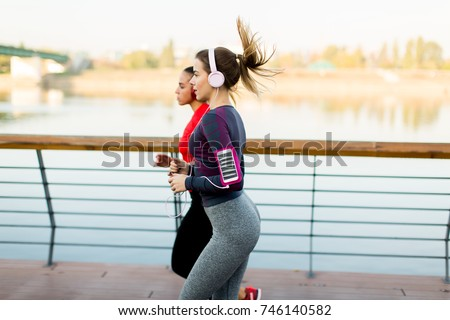 Two young women running by the river in the morning #746140582