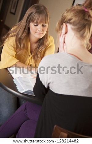 Two young women sit and study the bible together.