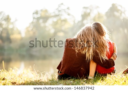 Shutterstock two young women sitting on grass hugging rear view