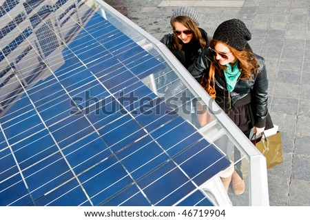 Two young women standing next to a solar powered tuc tuc