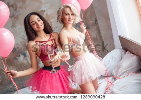 28710260c8 Two young women standing on bed at home wearing bra and sexy skirt holding  balloons and